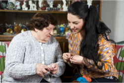 lady assisting an old woman in knitting thread